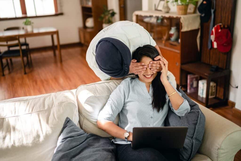 Couple d'origine indienne, heureux, surprise, assis canapé devant ordinateur